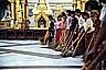 A row of volunteers sweeps the floor of Shwedagon Paya